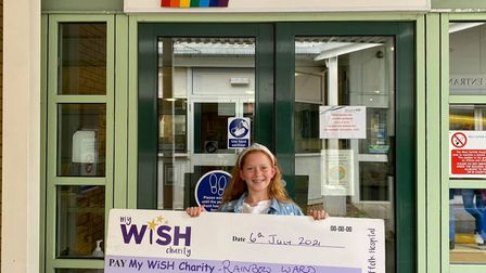 Maisie handing over the cheque to My WiSH