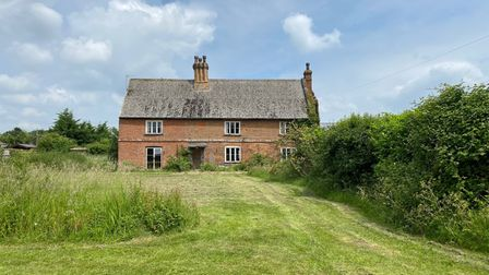 Large brick-built farmhouse set back off a large green lawn surrounded by hedges in Norfolk countryside