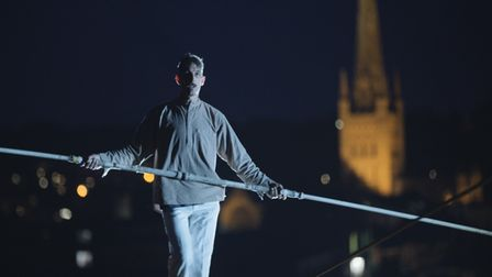 man on tightrope at night above city
