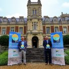 2 men standing in front of a stately home