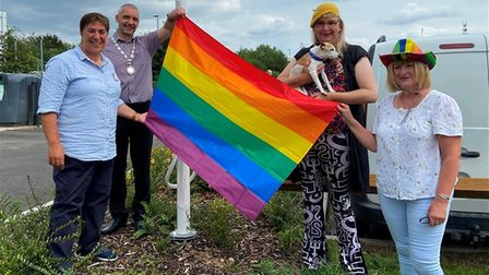 4 people holding a pride flag