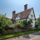 Large 17th century period farmhouse off a main road surrounded by a brick wall and shrubs