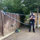 An officer stands by the alleyway cordon at the back of the property where two people were found dead