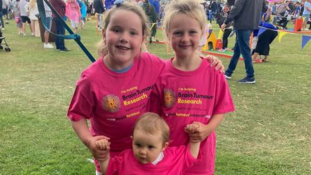 Betsy (left) with sisters Ava and Faith helped spread awareness of brain tumours in children at the Raver Tots festival