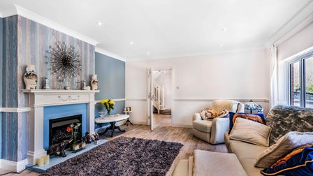 Light and airy reception room with blue feature fireplace, wood floors, rug, sofas and armchairs