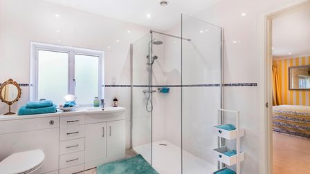 Contemporary shower room with double walk-in shower cubicle, tiled floor, white vanity