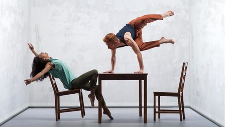 Two dancers, one leaning back on a chair, one leaping from the table