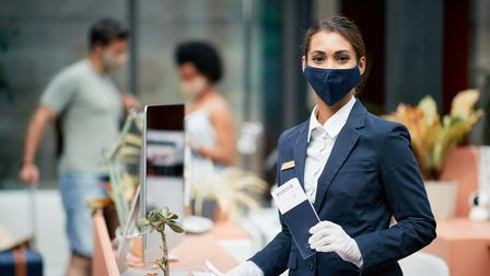 Portrait of happy hotel receptionist wearing face mask at work and looking at camera.