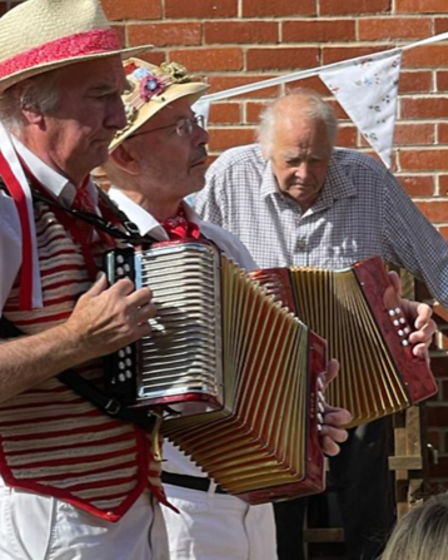 Two Morris men in their regalia play accordions with Clive, 94, at Moat Park in Great Easton