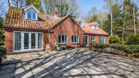 Brick-built chalet bungalow with patio doors opening onto a shaded sun terrace
