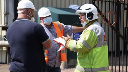 The fire incident commander talks to Banham Poultry staff outside the factory in Attleborough after