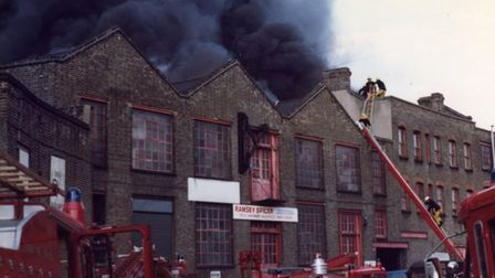 Firemen snapped in the roof tackling blazing warehouse in Wharf Place