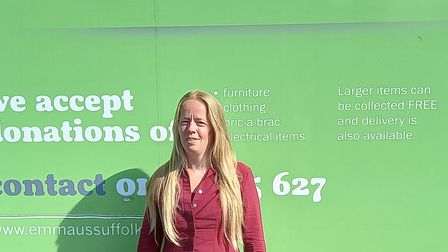 Amy standing in front of a sign for Emmaus Suffolk, a charitable organisation for homelessness