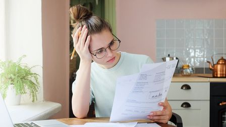 Indoor shot of young European Caucasian girl looking at financial documents at home with deeply bore