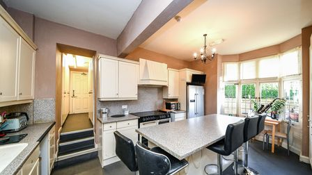 Kitchen with large breakfast bar with five stools, oven with extractor and steps leading up to inner hall