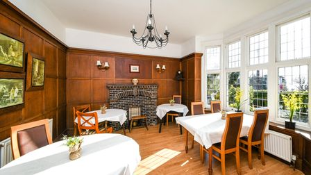 Panelled dining room with four individual tables, wood floor, large bay window and feature fireplace