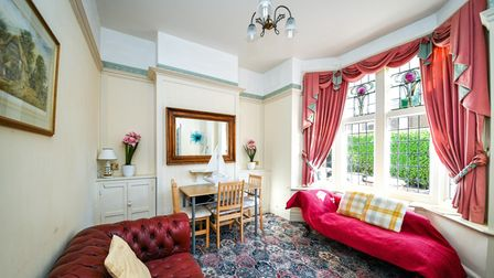 Sitting room with two sofas, table, chairs, red curtains in a bay window with rose-inspired stained glass