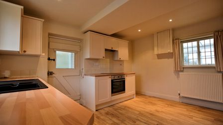 Shaker-style kitchen with wooden floors, worktops, electric hob and window