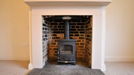 Cast iron log burner sent into a brick and stone hearth with cream coloured surround in an unfurnished sitting room