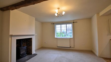 Large sitting room with cast iron log burner in a brick hearth and exposed beam across the ceiling