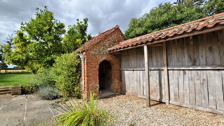 Brick built outbuilding with arched entrance on a shingle path next to a patio terrace