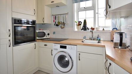 Small kitchen with Shaker-style units, washing machine, electric eye-level cabinet and clean white tiling