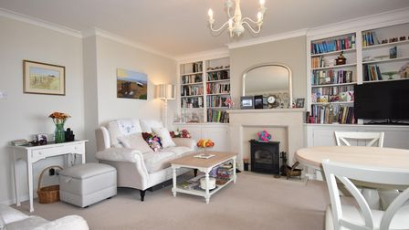 Large reception room with built-in alcove book shelving, sofa, table, chairs and carpeted floor