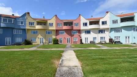 Row of five pastel colourfully painted apartments with communal lawn gardens at the front