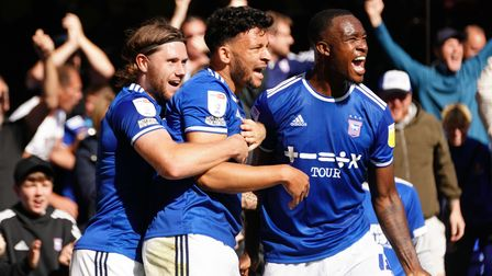 Wes Burns and Rekeem Harper celebrate with Macauley Bonne after he had scored to secure a draw for T