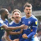 Kane Vincent-Young and Wes Burns celebrate with Scott Fraser after he had scored to level the game 1