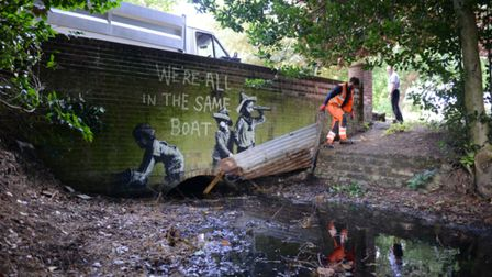 A man in orange overalls removes part of a piece of street art which has appeared on a wall in Nicho