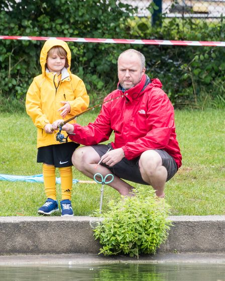Two people - a man and a boy - dressed in brightly coloured rain coats at the Doctor's Pond, Dunmow