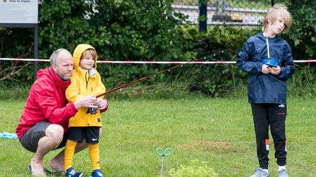 In the main image, three people in rain macs are fishing in Doctors Pond, Dunmow.