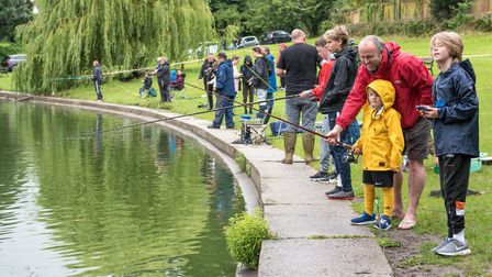 A large group of people line up on the edge of Doctors Pond in Great Dunmow, Essex - They are fishing