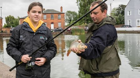 A girl with a fishing rod next to the tutor who unhooks her catch from the rod in Great Dunmow, Essex.