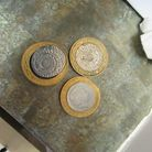 Three £2 coins on a table. Two of them have serious blemishes and flaws. They are counterfeit.