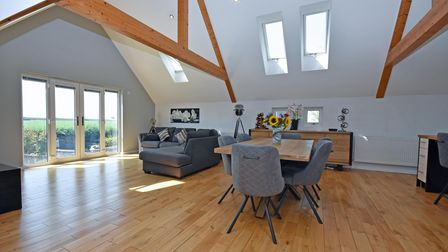 A large room with exposed beams, table and chairs, corner sofa, and doors with views to the countryside