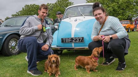 A light blue BMW Isetta car at Saffron Walden Motor Show 2021. There are two orange dogs in front.