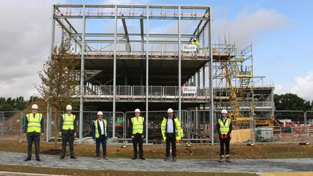 Men in hard hats standing in front of the steel frame of the new Great Notley Enterprise Centre, Essex