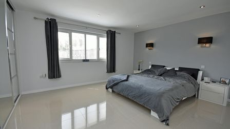 A bedroom with tiled floor, mirrored doors to built-in wardrobes and a bed with grey bedding on