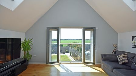 French doors open with views of the garden and fields