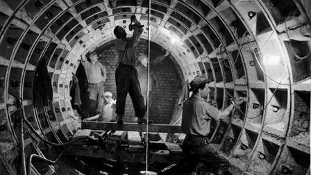 Workers applying caulking to joints in the sewer tunnel beneath Grapes Hill before brick lining in 1957.