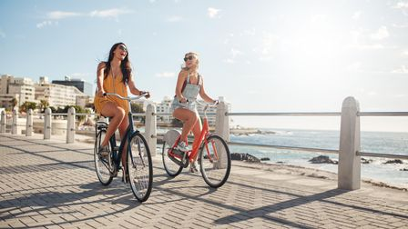 Two female friends cycling at Suffolk County Council