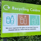 """A green sign reads: """"Recycling Centre: We no separate the glass so you don't have to"""""""