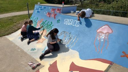 Young people working on repainting the skate park at Wells.