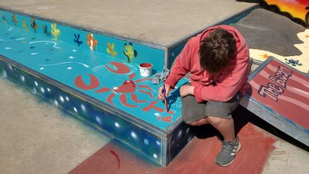 Max Zebedee works on a painting at the skatepark in Wells.
