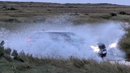 A car driving along the flooded road by the marshes which leads to the Brancaster Beach Car Park.