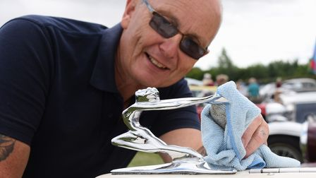 The grill sculpture on a Beauford is polished by owner Nigel Whitworth at the classic car show at St
