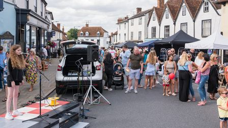 A street scene of a young woman with a microphone, and crowds at Great Dunmow Summer Market, Essex