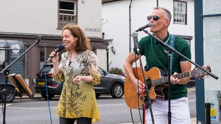 A singer and a singer playing guitar perform at Great Dunmow's Summer Market, Essex